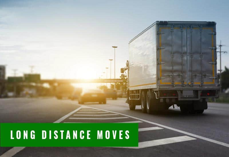 a highway intersection with vehicles and a moving truck moving someone long distance