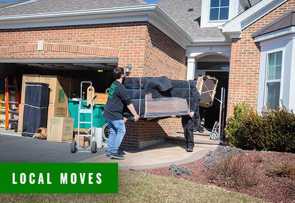 two movers carrying out a large sofa