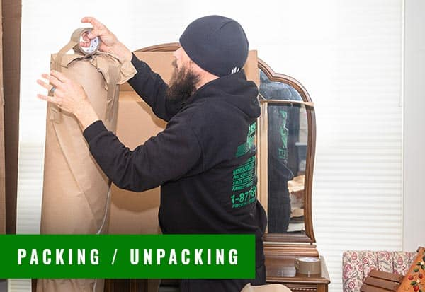 a trained moving expert packing and taping a carpet and large mirror dresser