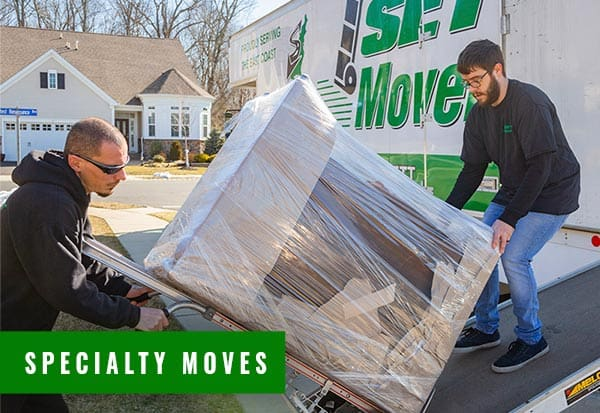 two movers unloading a specialty and heavy item off a moving truck